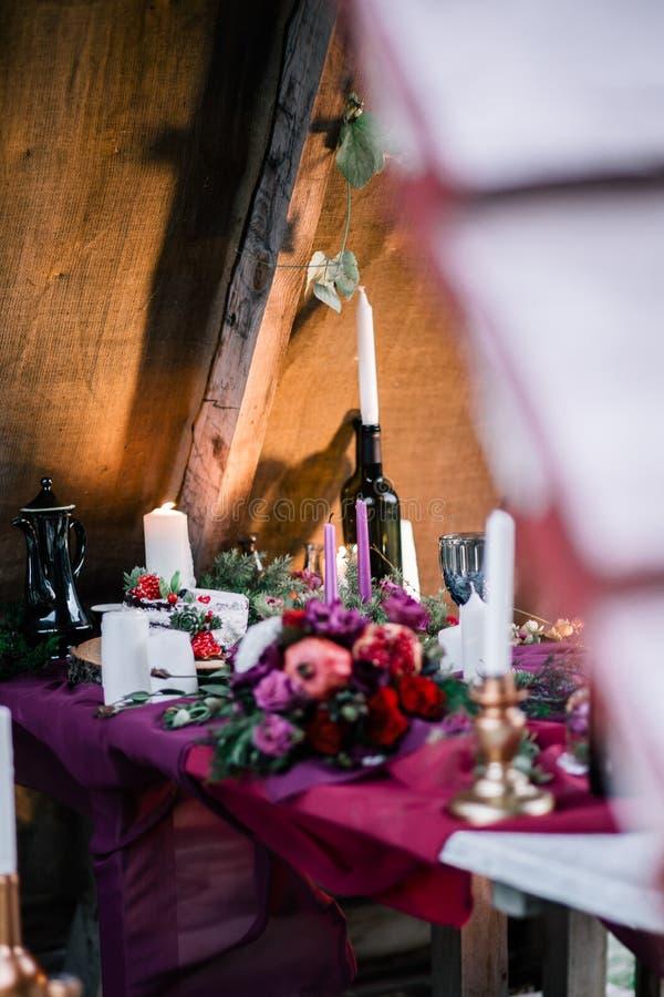 Empfindlicher heiratender weißer Kuchen verziert mit Granatapfel und saftiges umgeben durch Blumen und Kerzen stockfotos