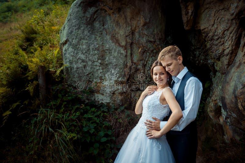 Empfindliches Hochzeitsporträt Hübscher Bräutigam, der weich die Brautrückseite auf den sonnigen Bergen umarmt lizenzfreie stockfotografie