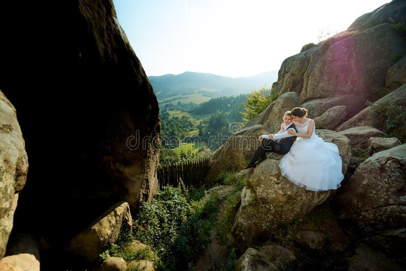 Empfindliches Hochzeitsporträt im Freien Die Braut umarmt den Bräutigam zurück beim Sitzen auf dem Felsen am Hintergrund von lizenzfreies stockbild