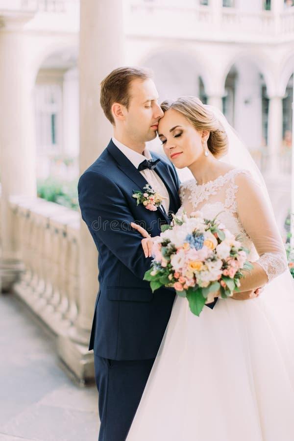 Empfindliches Porträt des Bräutigams, der die hübsche Brautrückseite umarmt stockfoto