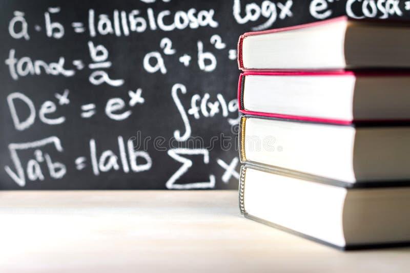 Empilez et pile des livres devant un tableau noir à l'école image stock