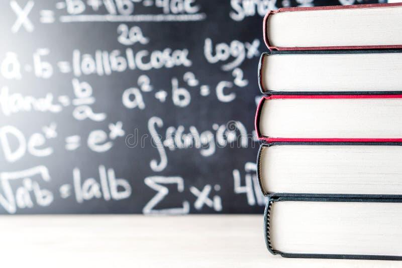 Empilez et pile des livres devant un tableau noir à l'école image libre de droits
