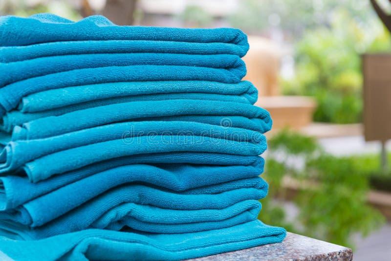 Empilez le rouleau de serviettes bleues de bain sur la table à la piscine photographie stock libre de droits
