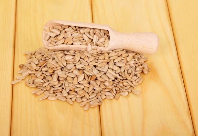 Empilez les graines de tournesol épluchées et le scoop en bois sur le bois léger photos libres de droits