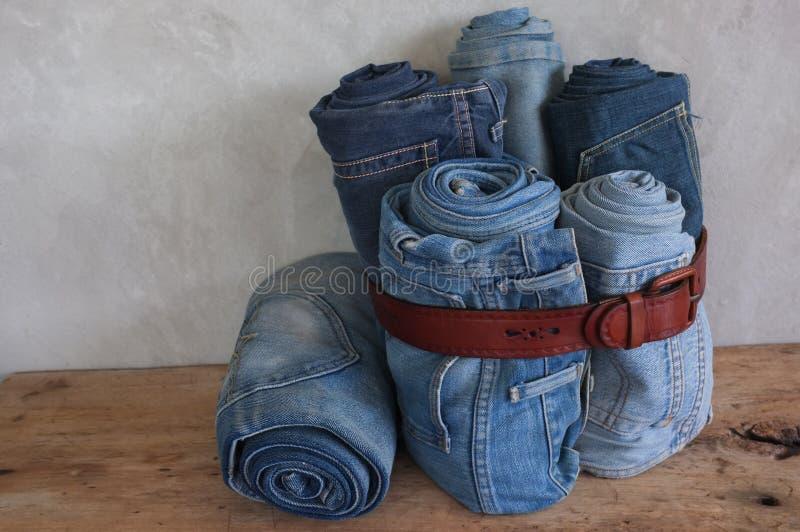 Empilez les jeans bleus de denim de petit pain et la ceinture en cuir sur le bois image libre de droits