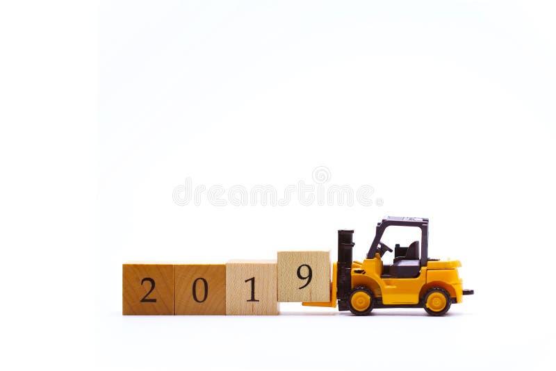 Empilhadeira amarela do brinquedo que levanta o bloco número de madeira 9 para terminar a palavra 2019 fotografia de stock royalty free