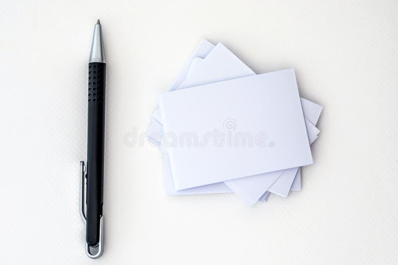 Empilhamento do cartão branco vazio do modelo com pena da elegância em um fundo do Livro Branco, um molde para a marcagem com fer imagens de stock royalty free
