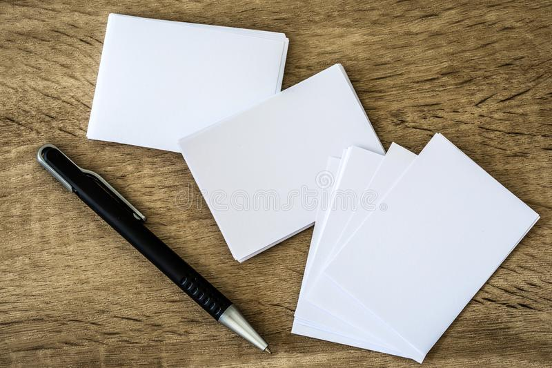Empilhamento do cartão branco vazio do modelo com uma pena da elegância no fundo de madeira, molde para a identidade de marcagem  fotografia de stock royalty free