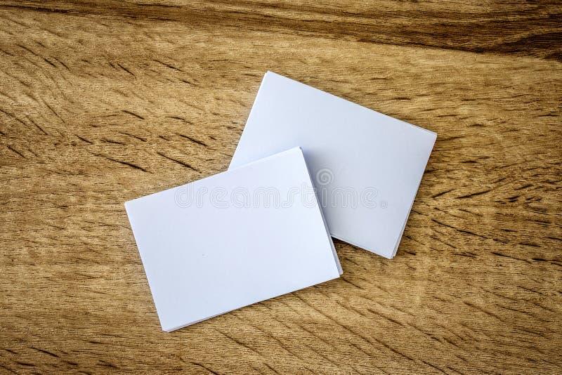 Empilhamento do cartão branco vazio do modelo no backgrou de madeira fotografia de stock