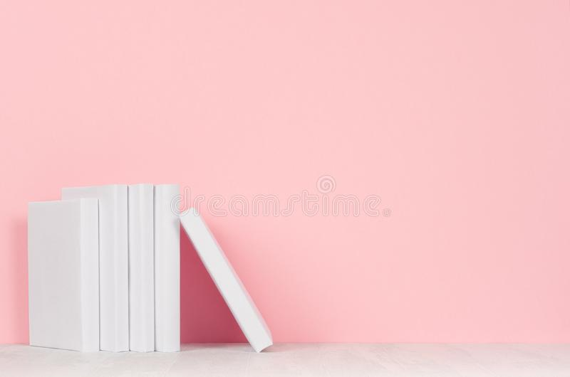 Empilhe livros brancos vazios no fundo da mesa branca e do rosa pastel imagem de stock