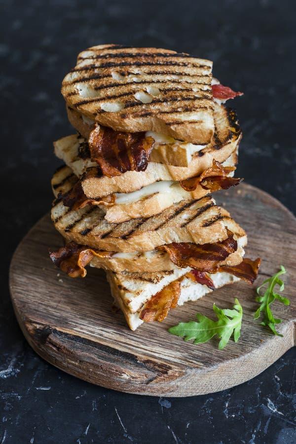 Empilhe o bacon grelhado, sanduíches da mussarela em placas de corte de madeira no fundo escuro, vista superior Pequeno almoço de fotos de stock