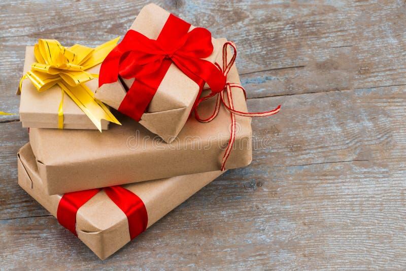 Empilhe presentes no papel de embalagem com a fita vermelha do cetim no backgr de madeira imagens de stock