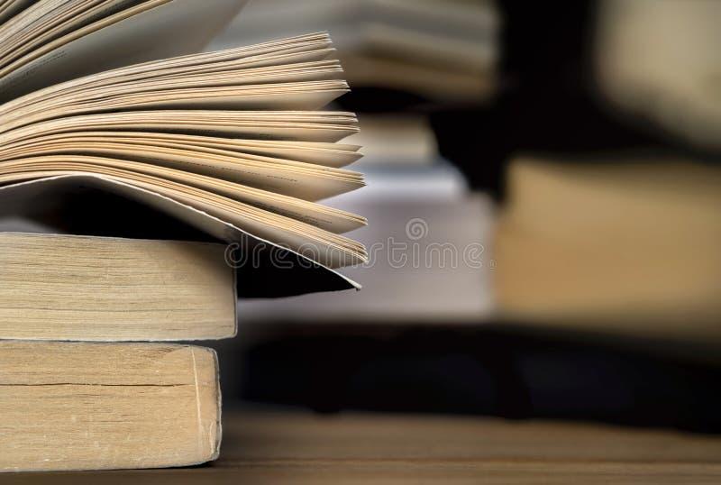 Empilhou livros e borram o fundo na tabela de madeira fotografia de stock royalty free