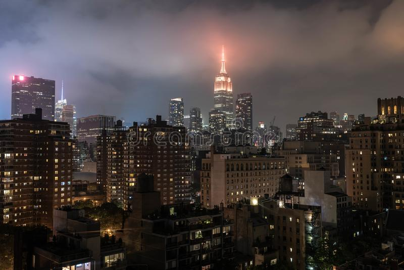 Empire state building foggy views at night time stock photography