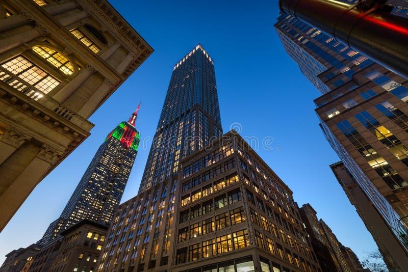 Empire State Building som är upplyst med julljus på skymning Skyskrapor på den 5th avenyn, Midtown Manhattan, New York royaltyfria foton