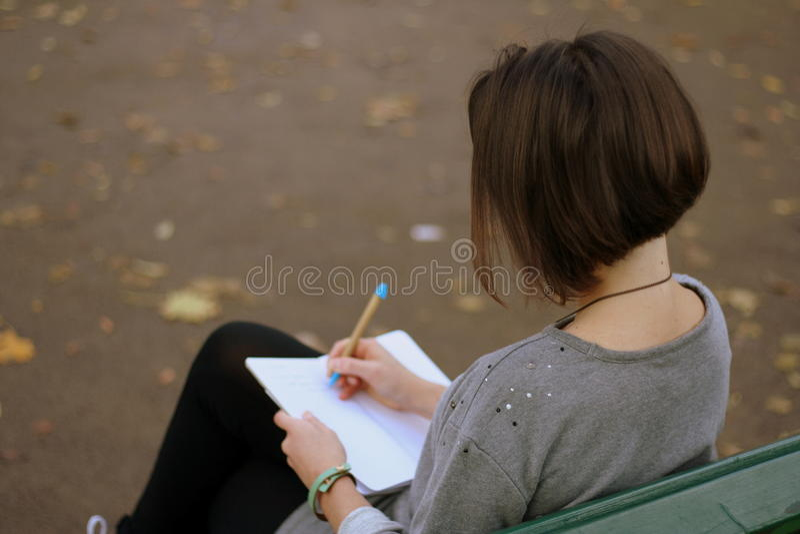 Emplacement de fille de brune sur le banc de parc et les notes d'écriture dans son bloc-notes Photo par derrière photos libres de droits