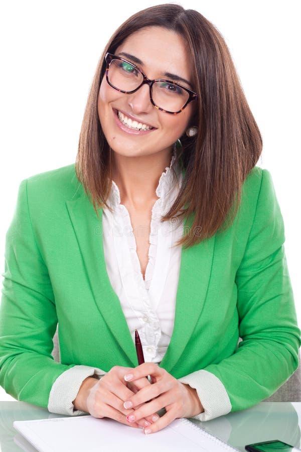 Emplacement de jeune femme à un bureau utilisant une veste verte photographie stock libre de droits