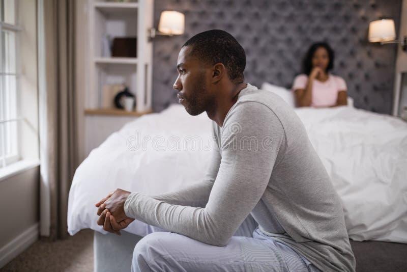 Emplacement de jeune homme tandis que femme se reposant sur le lit à la maison photographie stock