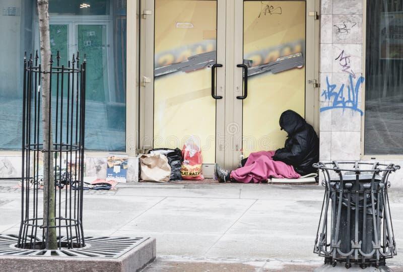 Emplacement sans abri d'homme en temps froid à la boutique fermée de porte dans Wrocl photos stock