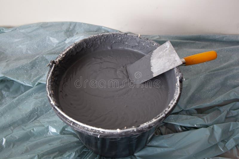 Emplastro decorativo e uma pá de pedreiro em uma cubeta imagem de stock