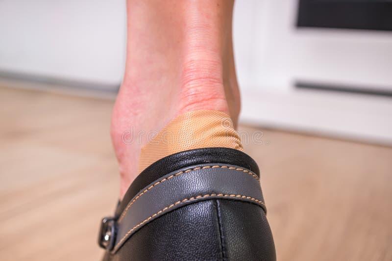 Emplastro esparadrapo no salto do ` s da mulher - sapatas incômodas imagens de stock royalty free