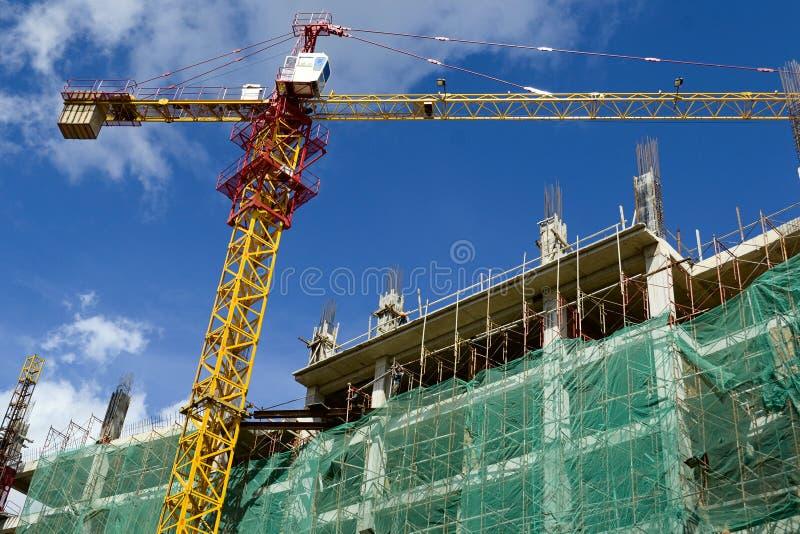 Emplazamiento de la obra con la grúa amarilla y edificio en un fondo del cielo azul imagenes de archivo