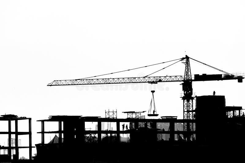 Emplazamiento de la obra con las grúas en fondo de la silueta imagen de archivo
