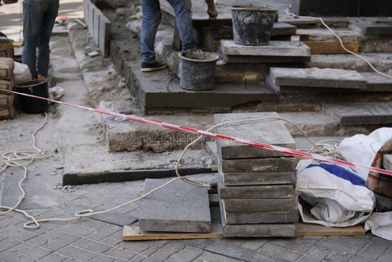 Emplazamiento de la obra con las losas y el trabajador en fondo imagen de archivo