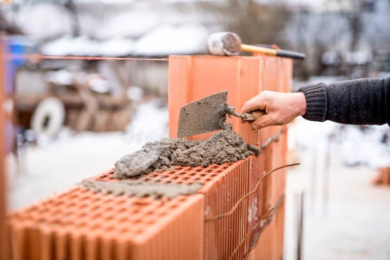 Emplazamiento de la obra con las paredes de ladrillo del edificio del trabajador con el mortero y los ladrillos imágenes de archivo libres de regalías