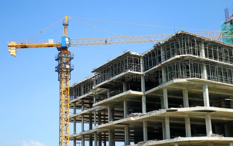 Emplazamiento de la obra concreto del Highrise, con grúa, cielo azul fotografía de archivo