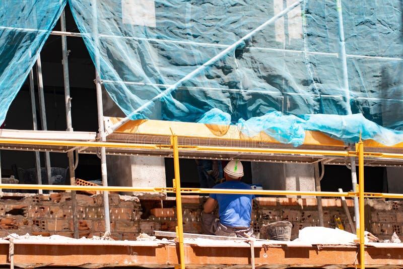 Emplazamiento de la obra de la construcción de viviendas vieja con el andamio y un trabajador ocupado del albañil Tapiado del alb foto de archivo libre de regalías