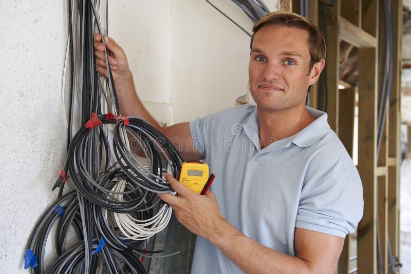Emplazamiento de la obra de Fitting Wiring On del electricista imágenes de archivo libres de regalías