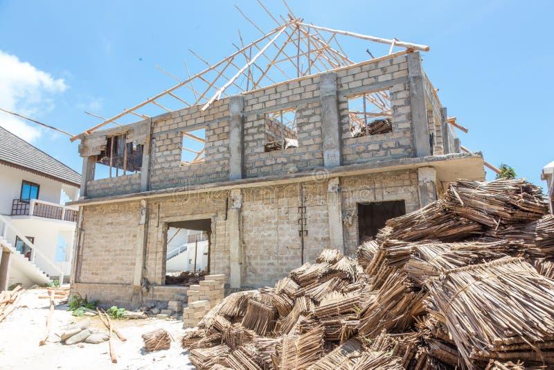 Emplazamiento de la obra del tejado tradicional que cubre con paja en África El convertirse del genio civil tached tradicional de imagenes de archivo