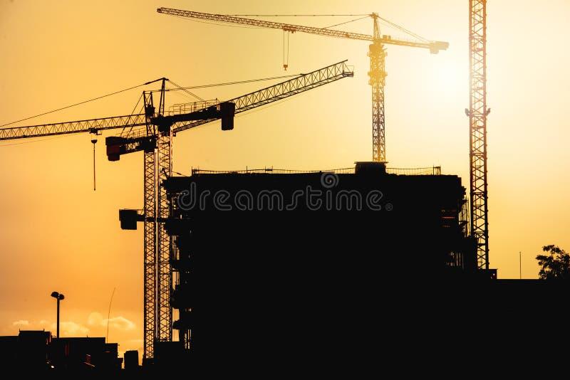 emplazamiento de la obra en la puesta del sol con las siluetas grúa fotografía de archivo libre de regalías