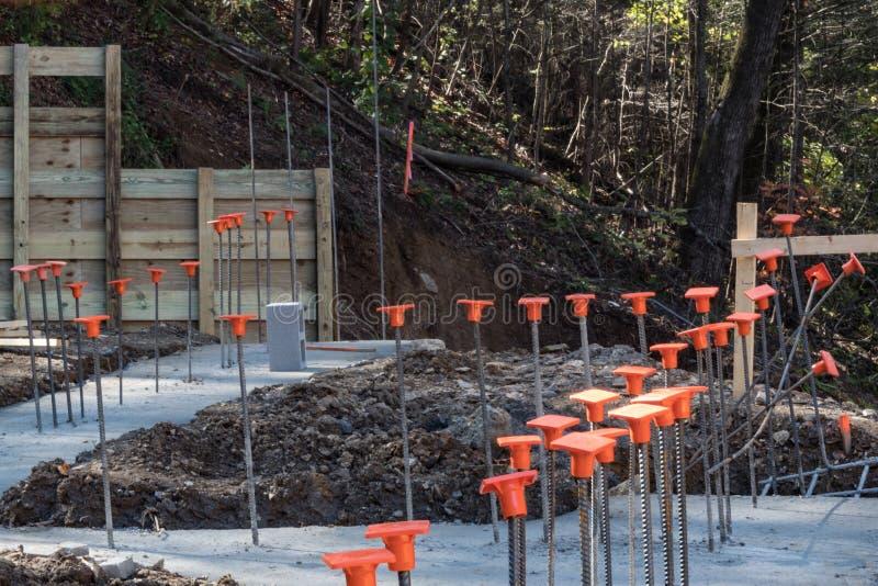 Emplazamiento de la obra en la ladera con los pies vertidos y el rebar con los casquillos de seguridad anaranjados fotografía de archivo