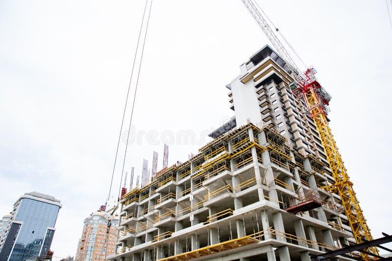 Emplazamiento de la obra Grúa industriales grandes con alto inacabado aumentaron edificios y el cielo azul en fondo andamio moder fotografía de archivo