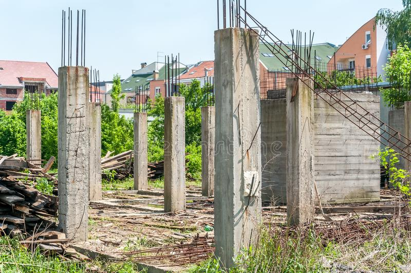 Emplazamiento de la obra inacabado abandonado del edificio o de la casa con los detalles arquitectónicos de los polos concretos a fotos de archivo