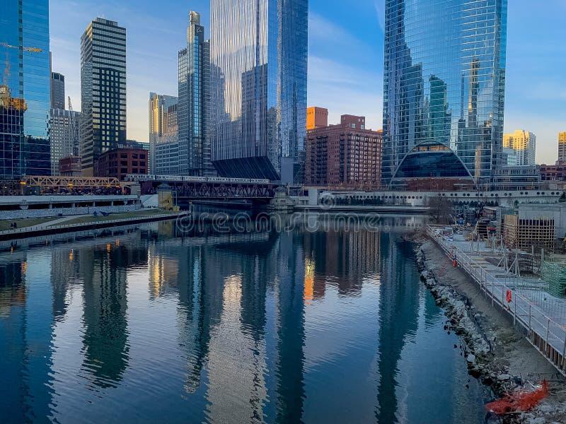 Emplazamiento de la obra junto a las aguas inmóviles del río Chicago, que están reflejando paisaje urbano de alrededor imagen de archivo