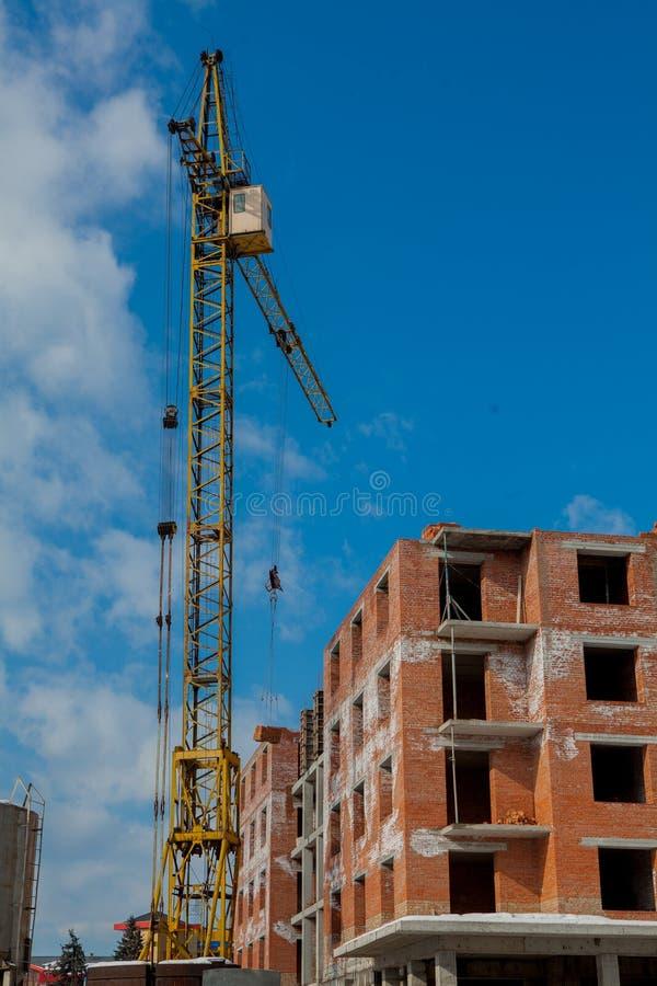 Emplazamiento de la obra de un alto edificio del nuevo apartamento con grúa contra el cielo azul Desarrollo del área residencial  fotografía de archivo