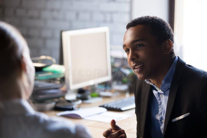Empleado africano que habla con el colega femenino que se sienta junto en el lugar de trabajo imagen de archivo libre de regalías