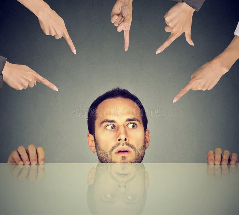 Empleado asustado del hombre que oculta debajo de la tabla que es acusada por mucha gente que señala los fingeres en él fotos de archivo libres de regalías