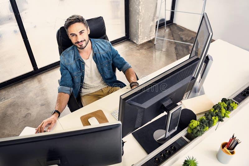 Empleado barbudo sonriente que trabaja en el apartamento cómodo imágenes de archivo libres de regalías