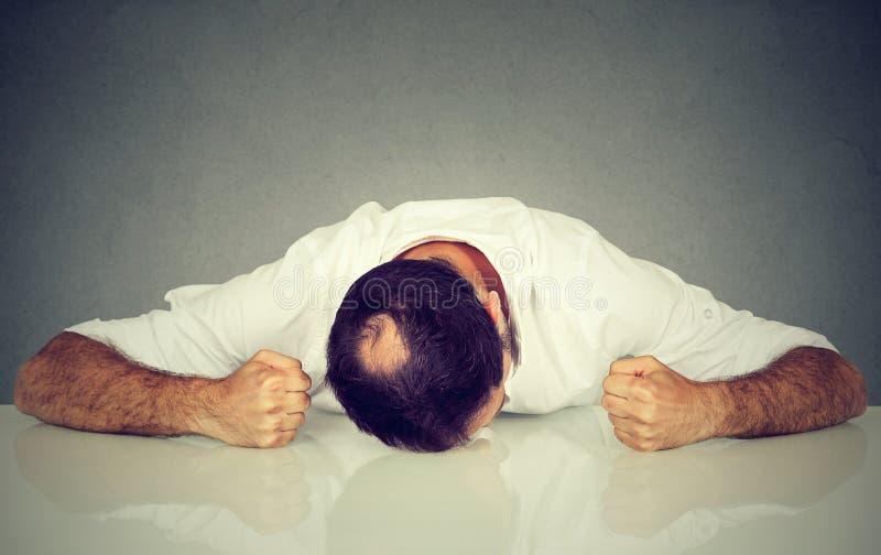 Empleado cansado, subrayado del hombre que duerme en una tabla imagen de archivo libre de regalías
