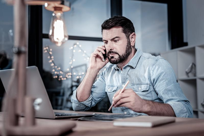 Empleado confiable ocupado que tiene conversación telefónica y que usa su ordenador portátil fotos de archivo libres de regalías