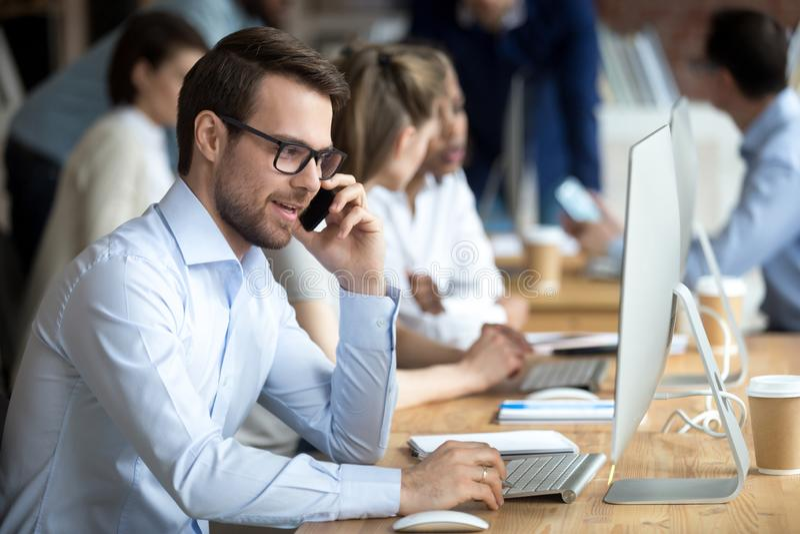 Empleado confiado que habla por el teléfono con el cliente, cliente foto de archivo