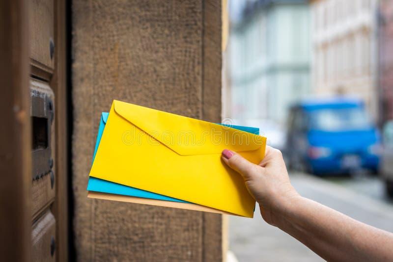 Empleado de correos que inserta el sobre en ranura de correo fotografía de archivo libre de regalías