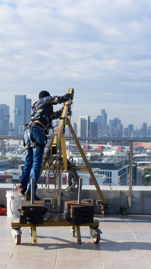 Empleado de la limpieza de ventana con las herramientas del trabajo y el fondo de la ciudad foto de archivo libre de regalías