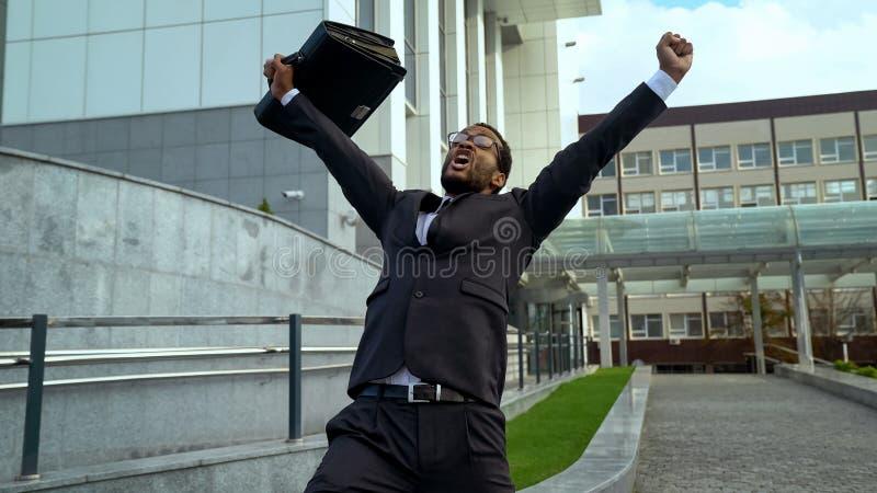 Empleado de oficina feliz mismo del mulato que grita alegre, éxito de la promoción de la carrera imagen de archivo libre de regalías
