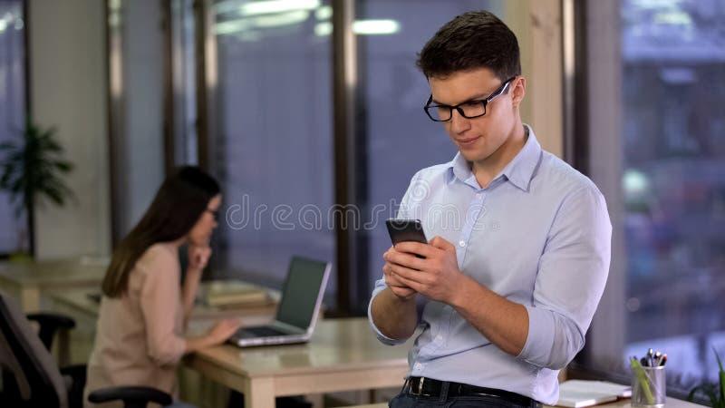 Empleado de oficina que charla en mensajero social de los medios en el smartphone, comunicaci?n fotos de archivo