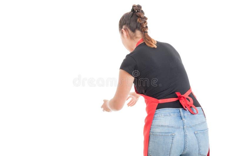 Empleado de sexo femenino con el delantal que coge algo imagenes de archivo